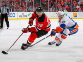 Patrik Elias of the New Jersey Devils plays the puck against Anders Lee of the New York Islanders during the game at the Prudential Center on April...