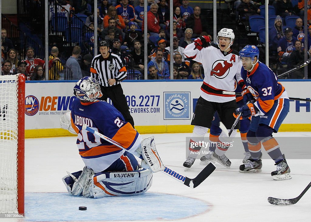 Patrik Elias #26 of the New Jersey Devils reacts to the game winning goal by David Clarkson #23 (not pictured) as goaltender <a gi-track='captionPersonalityLinkClicked' href=/galleries/search?phrase=Evgeni+Nabokov&family=editorial&specificpeople=171380 ng-click='$event.stopPropagation()'>Evgeni Nabokov</a> # 20 of the New York Islanders looks away during the Islanders home opener at the Nassau Coliseum on January 19, 2013 in Uniondale, New York.