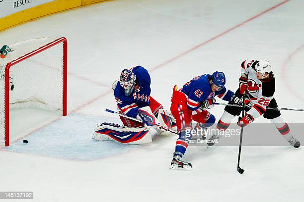 Patrik Elias of the New Jersey Devils scores a first period goal past Artem Anisimov and Henrik Lundqvist of the New York Rangers in Game Five of the...