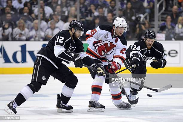 Patrik Elias of the New Jersey Devils skates against Simon Gagne and Colin Fraser of the Los Angeles Kings Game Four of the 2012 Stanley Cup Final at...