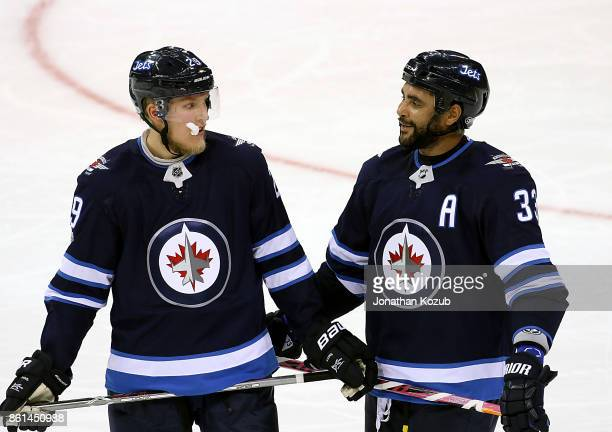 Patrik Laine and Dustin Byfuglien of the Winnipeg Jets chat during a third period stoppage in play against the Carolina Hurricanes at the Bell MTS...