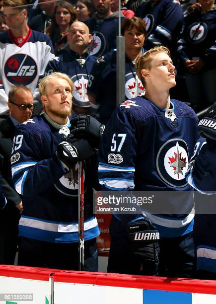 Patrik Laine and Tyler Myers of the Winnipeg Jets stand on the bench during the singing of the national anthems prior to puck drop against the...