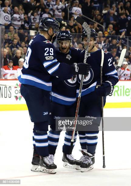 Patrik Laine Bryan Little and Nikolaj Ehlers of the Winnipeg Jets celebrate a first period goal against the Carolina Hurricanes at the Bell MTS Place...