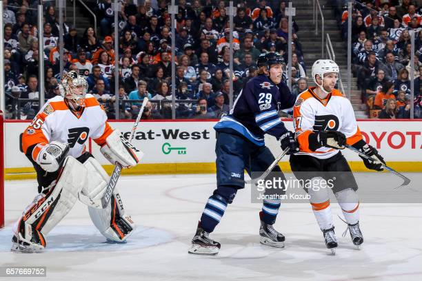 Patrik Laine of the Winnipeg Jets and Andrew MacDonald of the Philadelphia Flyers battle for space in front of goaltender Steve Mason as they keep an...