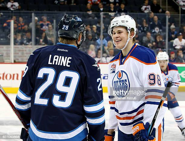 Patrik Laine of the Winnipeg Jets and Jesse Puljujarvi of the Edmonton Oilers chat during the pregame warm up prior to NHL action at the MTS Centre...