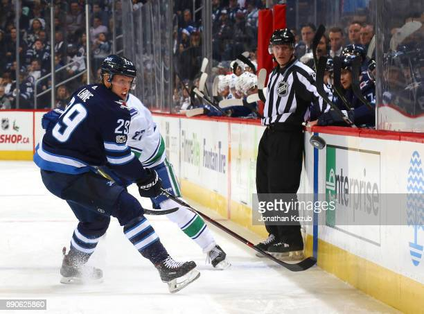 Patrik Laine of the Winnipeg Jets and Vaughan Rody watch as the puck flies down the ice during first period action against the Vancouver Canucks at...