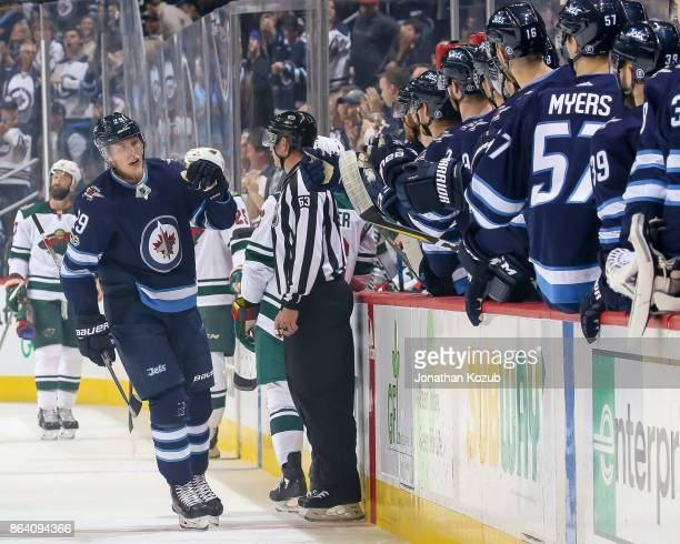 Patrik Laine of the Winnipeg Jets celebrates his first period goal against the Minnesota Wild with teammates at the bench at the Bell MTS Place on...