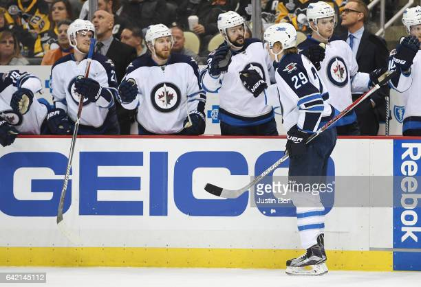 Patrik Laine of the Winnipeg Jets celebrates his goal with teammates on the bench in the second period during the game against the Pittsburgh...