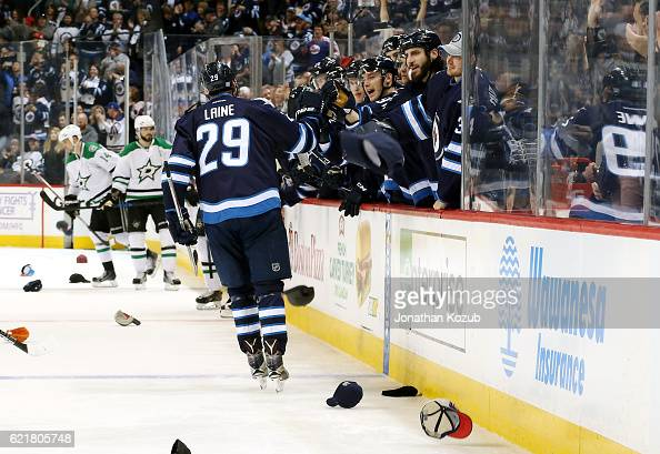Patrik Laine of the Winnipeg Jets celebrates his third goal of the night against the Dallas Stars with teammates at the bench while hats rain down on...