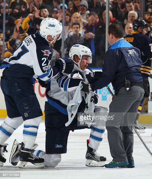 Patrik Laine of the Winnipeg Jets is helped off the ice by Nikolaj Ehlers and an athletic trainer after being injured during an NHL game against the...