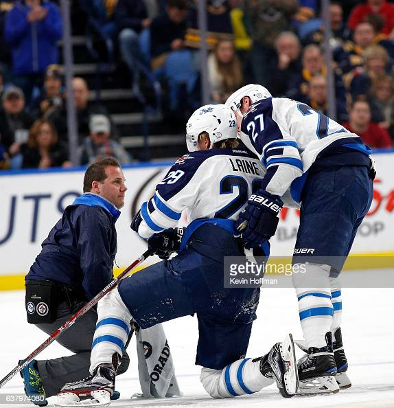 Patrik Laine of the Winnipeg Jets is helped to the ice by Nikolaj Ehlers and a trainer after being checked by Jake McCabe of the Buffalo Sabres...