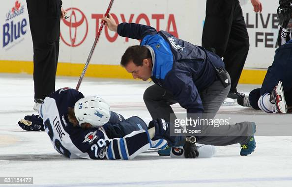 Patrik Laine of the Winnipeg Jets is tended to be a trainer after a third period check by the Buffalo Sabres during an NHL game at the KeyBank Center...