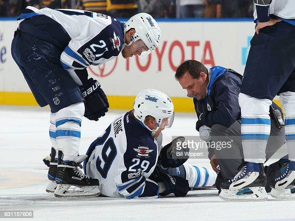 Patrik Laine of the Winnipeg Jets is tended to by by Nikolaj Ehlers and an athletic trainer after being injured during an NHL game against the...