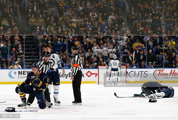 Patrik Laine of the Winnipeg Jets lays on the ice as Jake McCabe of the Buffalo Sabres is separated from Mark Scheifele of the Winnipeg Jets by...
