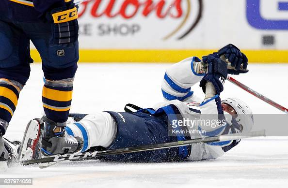 Patrik Laine of the Winnipeg Jets lays stiff unconscious after being checked by Jake McCabe of the Buffalo Sabres during the third period at the...