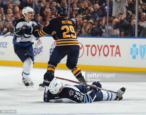 Patrik Laine of the Winnipeg Jets lies on the ice injured after a third period check by Jake McCabe of the Buffalo Sabres during an NHL game at the...