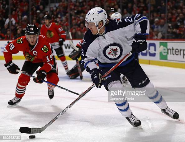 Patrik Laine of the Winnipeg Jets looks to pass as Jonathan Toews of the Chicago Blackhawks closes in at the United Center on December 27 2016 in...
