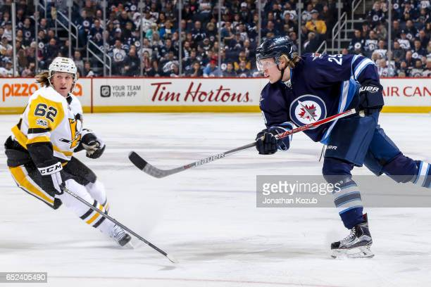Patrik Laine of the Winnipeg Jets shoots the puck towards the goal as Carl Hagelin of the Pittsburgh Penguins looks on during second period action at...