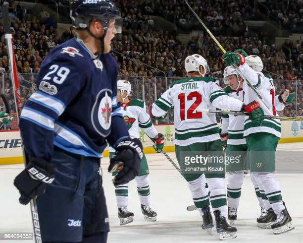Patrik Laine of the Winnipeg Jets skates away as Eric Staal of the Minnesota Wild celebrates a first period goal with teammates at the Bell MTS Place...