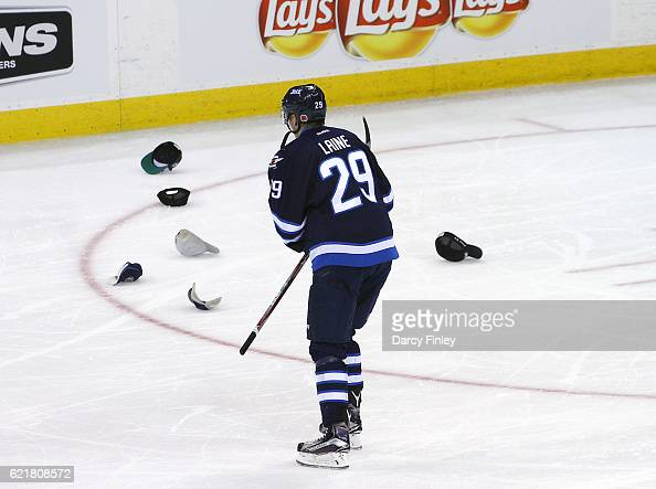 Patrik Laine of the Winnipeg Jets skates to the bench as hats litter the ice following his third goal of the night against the Dallas Stars during...