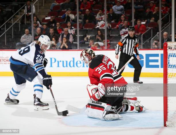 Patrik Laine of the Winnipeg Jets skates with the puck on his way to scoring the game winning goal during the shootout against Cory Schneider of the...