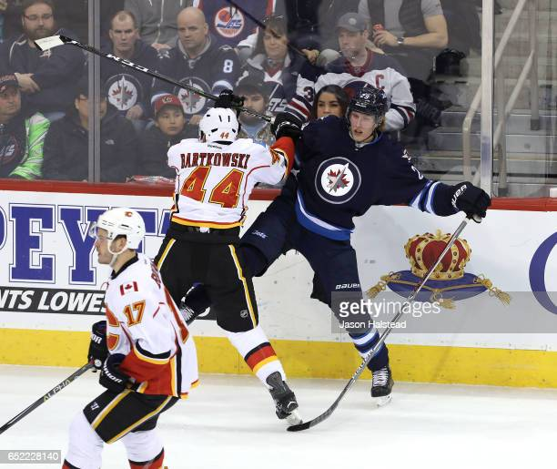Patrik Laine of the Winnipeg Jets takes a check from Matt Bartkowski of the Calgary Flames during NHL action on March 11 2017 at the MTS Centre in...