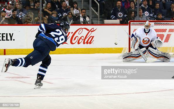 Patrik Laine of the Winnipeg Jets takes a shot on goal as goaltender Thomas Greiss of the New York Islanders guards the net during second period...