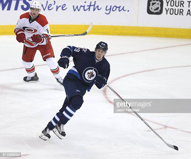 Patrik Laine playing his first NHL game of the Winnipeg Jets skates away from Noah Hanifin of the Carolina Hurricanes during NHL action on October 22...