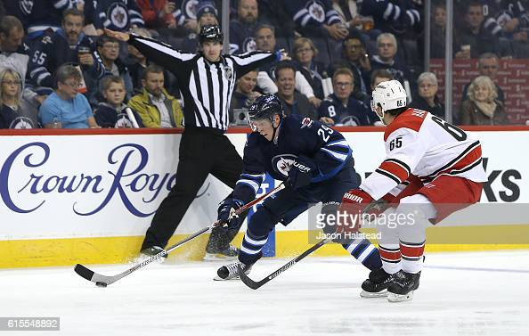 Patrik Laine playing his first NHL game of the Winnipeg Jets tries to get past Ron Hainsey of the Carolina Hurricanes during NHL action on October 22...