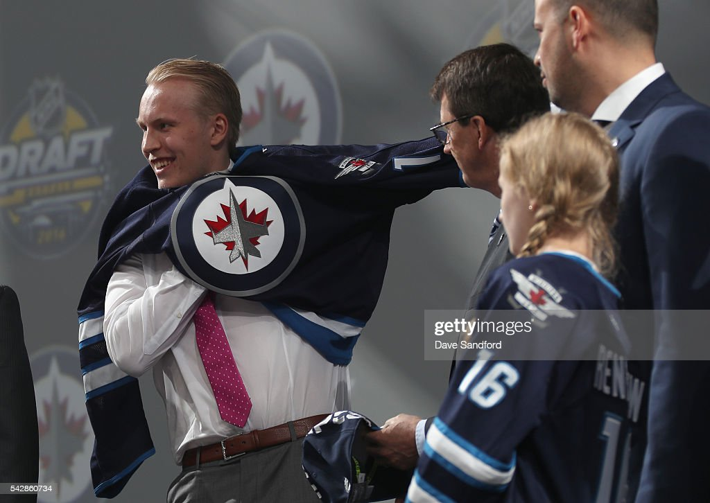 <a gi-track='captionPersonalityLinkClicked' href=/galleries/search?phrase=Patrik+Laine&family=editorial&specificpeople=13600427 ng-click='$event.stopPropagation()'>Patrik Laine</a> puts on his jersey onstage after being selected second overall by the Winnipeg Jets during round one of the 2016 NHL Draft at First Niagara Center on June 24, 2016 in Buffalo, New York.