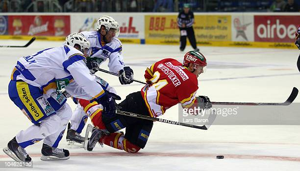Patrik Vogl and Johan Ejdepalm of Muenchen hold Martin Hinterstocker of Duesseldorf during the DEL match between DEG Metro Stars and EHC Muenchen at...
