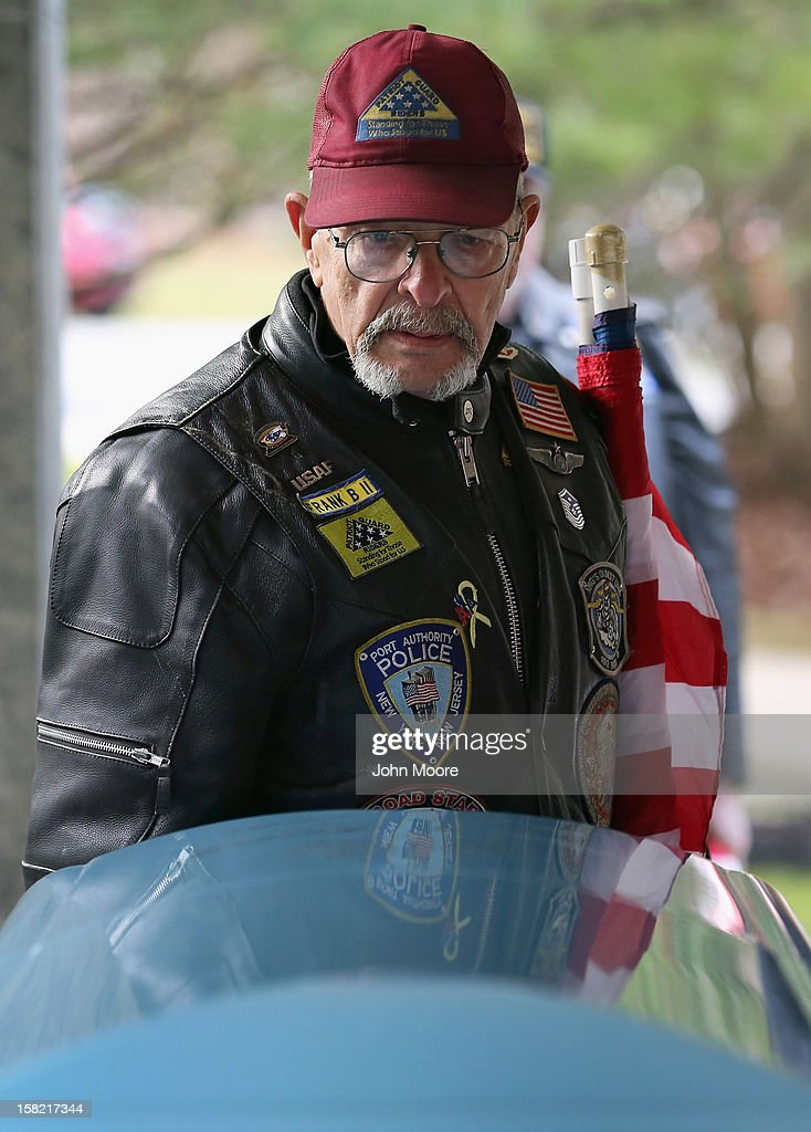 A Patriot Guard rider pays his last respects over the casket containing the body of Hurricane Sandy victim David Maxwell at the Calverton National Cemetery on December 11, 2012 near the Wading River hamlet of Long Island, New York. Maxwell, 66, was the last of Sandy's victims found on the Staten Island borough of New York City, when his body was discovered in his Midland Beach home 11 days after the storm. A Vietnam veteran, he was buried at the national cemetery, accompanied by honor guards from the Catholic War Veterans and the Patriot Guard Riders.