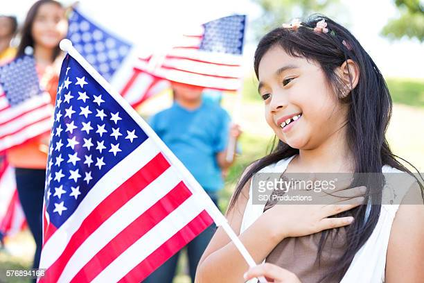 Patriotic Asian American girl with her hand over her heart
