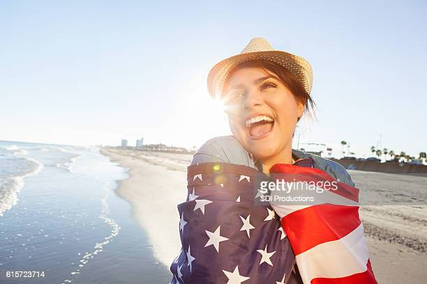 Patriotic Hispanic woman wrapped in US flag on the beach