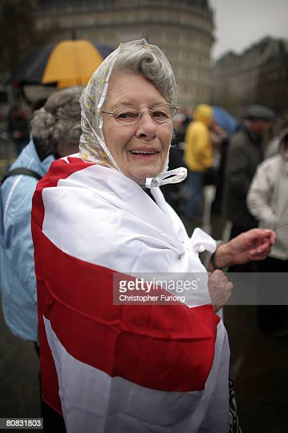 A patriotic lady draped in a St George flag and resplendent in a plastic rain hat braves the rain to watch the festivities celebrating Saint...