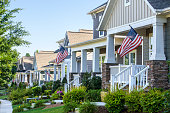 American Flags hang from the front porch of a row of upscale Victorian-style homes in celebration of the upcoming holiday. Taken in the Summer in North Carolina, with beautiful morning sunlight to cel