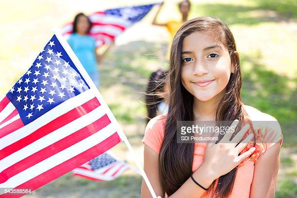 Patriotic preteen Hispanic little girl with American Flag
