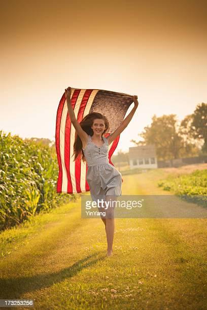 Patriotische Teen Farm Mädchen läuft über Feld winken uns Flagge