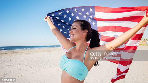 Patriotic woman with American flag on the beach