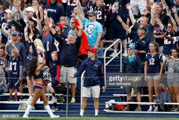 Patriots cheerleader tossesa teeshirt to the fans during New England Patriots training camp on July 27 at the Patriots Practice Facility in...