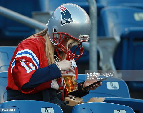 Patriots fan wearing a helmet checked her cell phone in the stands before the New England Patriots hosted the Philadelphia Eagles in a regular season...