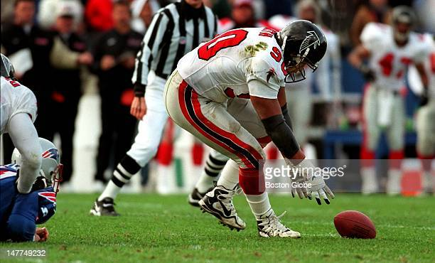 Patriots quarterback Drew Bledsoe lies helpless on the Foxboro Stadium turf at left as he watches the Falcons' defensive left end Chuck Smith scoop...