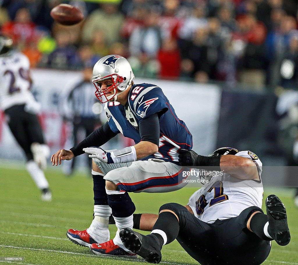 Patriots quarterback Tom Brady gets rid of the ball as the Ravens' Haloti Ngata pulls him down for an incomplete pass as the New England Patriots hosted the Baltimore Ravens in the AFC Championship Game at Gillette Stadium.