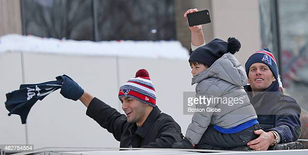 Patriots quarterbacks Jimmy Garoppolo left and Tom Brady right enjoy the Patriots Super Bowl victory parade with Brady's son Benjamin from atop a...