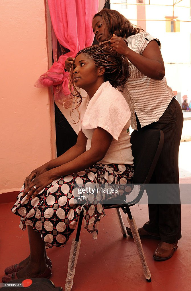 Patritia Sei (R), a 22-year-old Ivorian refugee, styles a costumer's hair at her shop, on June 18, 2013, in Rabat. Thousands of refugees living in Morocco are facing a common dilemma -- whether to leave the transit country for Europe or push for further exile.