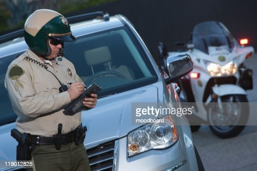 Patrol officer stands witing ticket : Foto stock