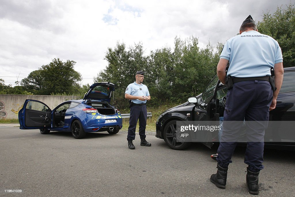 A patrol working with the new interceptor car of the French Gendarmerie, a Megane IIIS from French car manufacturer Renault, fines a driver for speeding, on the motorway between Paris and Saint-Arnoult-en-Yvelines, west of Paris, on July 18, 2011. The car, will be used by the Gendarmerie (military police), and will replace progressively their Subaru Impreza.