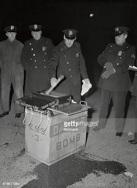 A patrolman of New York's Emergency Squad examines contents of mysterious 'bomb' found at manhattan Center during a teacher's meeting The photo shows...