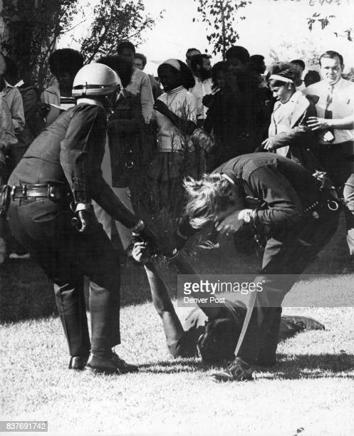 Patrolman Richard G Nelsen Right Staggers after being struck by an Object in School Fray He and other officers were dragging apparently unconscious...