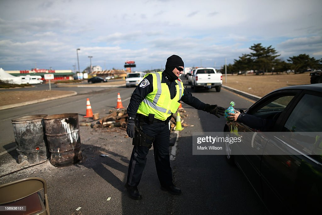 Patrolman Ryan Greenhalgh is given a bag of cookies while working a check point to make sure only residents and contractors enter on November 24, 2012 in Ortley Beach, New Jersey. New Jersey Gov. Christie estimated that Superstorm Sandy cost New Jersey $29.4 billion in damage and economic losses.